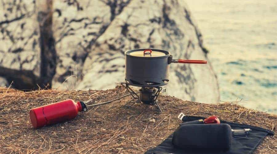 backpacking stove and pot sitting on cliff edge intext