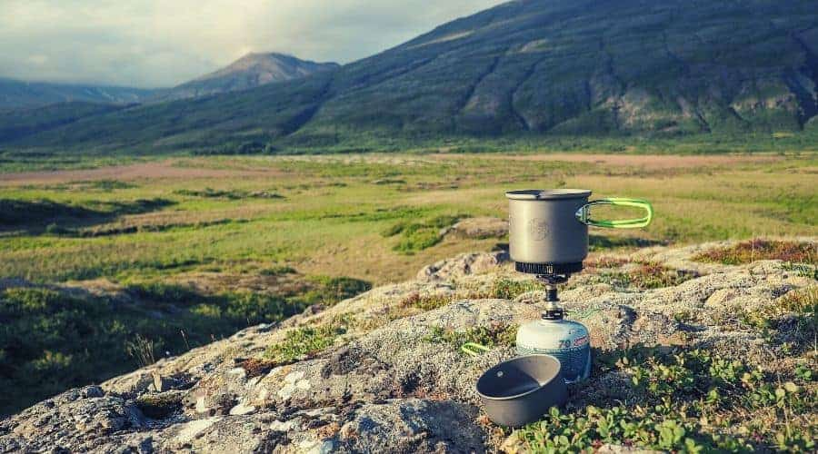 backpacking stove and pot sitting overlooking valley intext