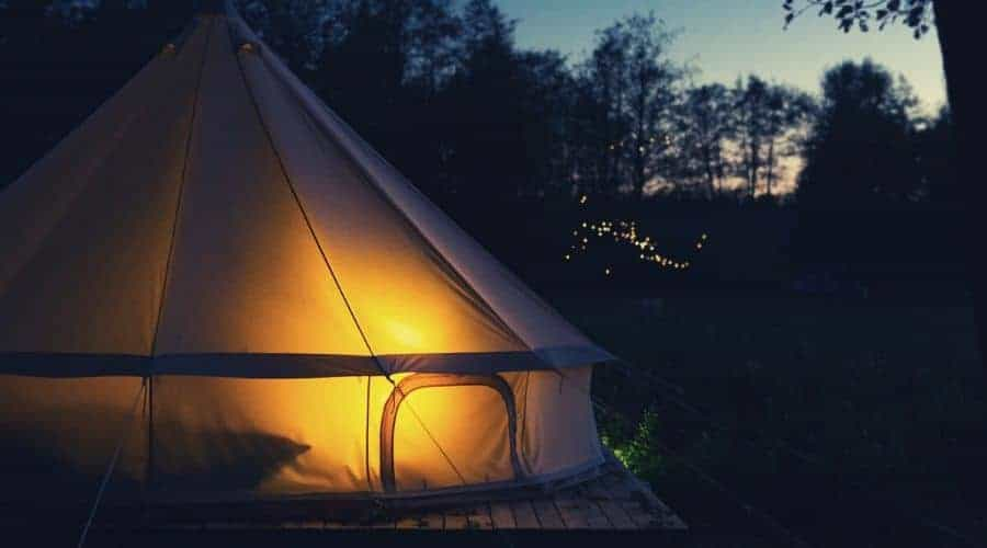 large bell tent in the dark illuminated by lantern