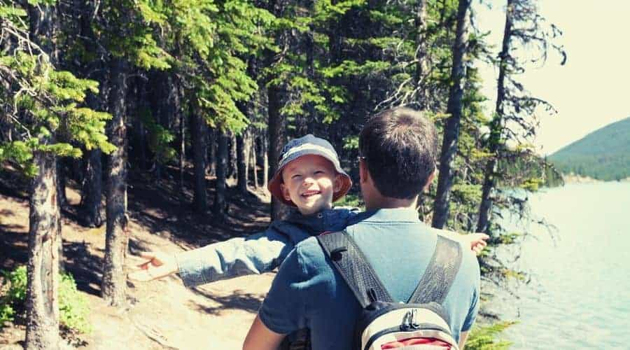 happy boy carried by father on hiking trip