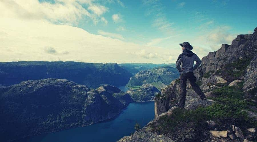 Man hiker looking over fjord panorama intext