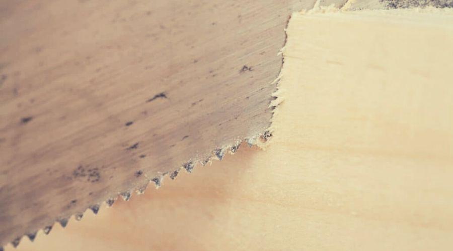 Hand saw cutting through a beam of wood intext