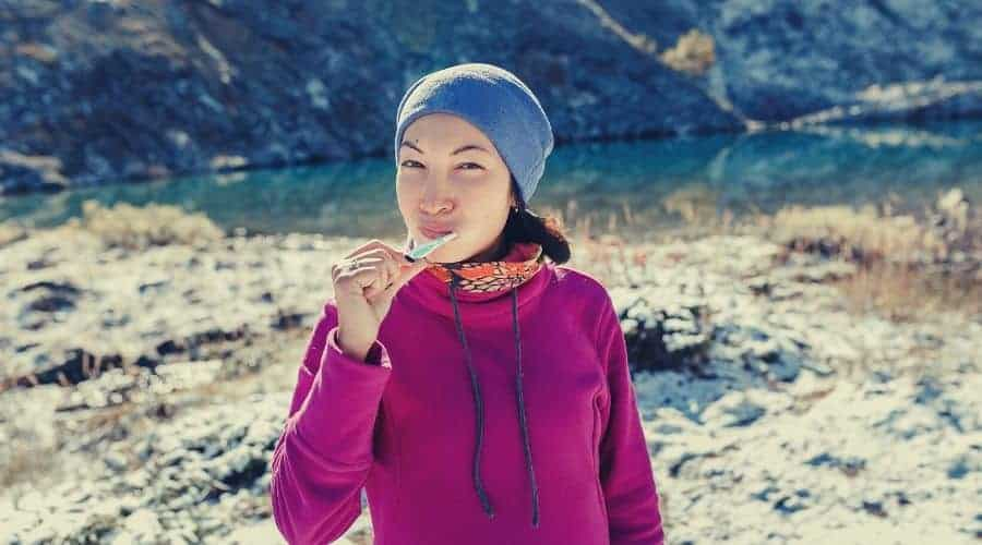 backpacker brushing teeth at mountainside camp