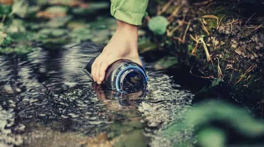 hiker filling nalgene bottle from sream intext