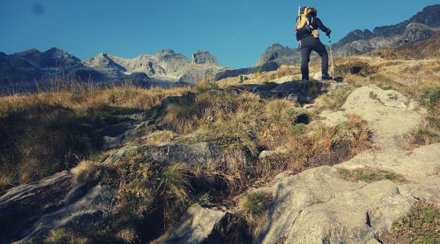 hiker walking towards cairn intext