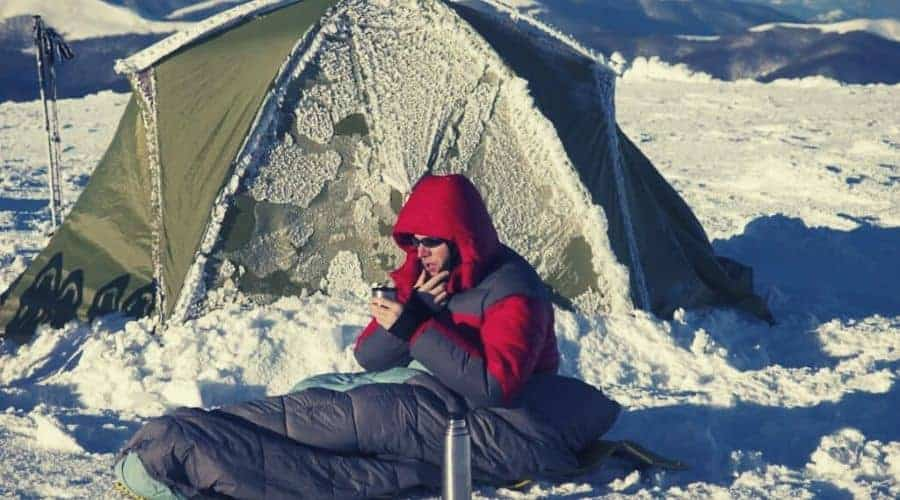 man sitting outside tent in the snow in sleeping bag intext
