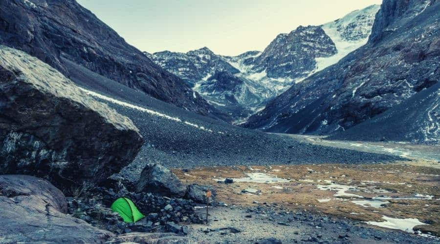 green backpacking tent in rocky valley in mountains