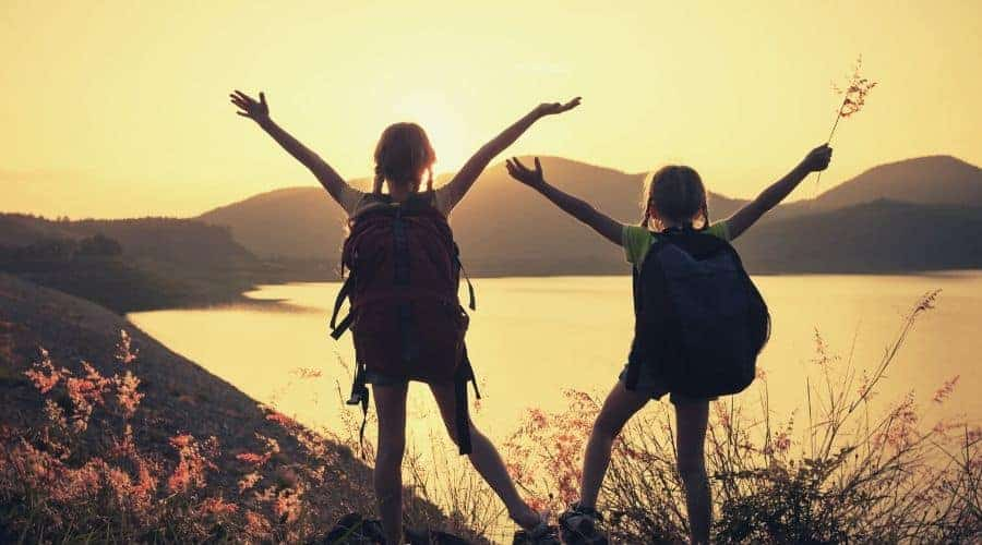 silhoutte of two girls hiking lake intext