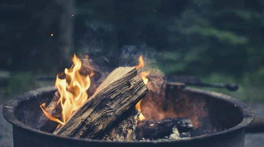 Fire roaring in a metal fire pit intext