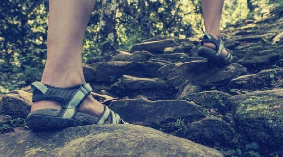 hiker climbing stone trail in hiking sandals intext