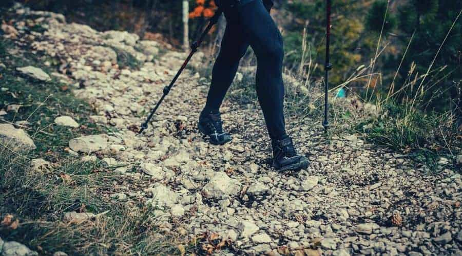 Woman hiking in trail of stones with leggings and hiking poles
