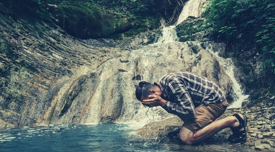 male hiker washes face in waterfall pool intext