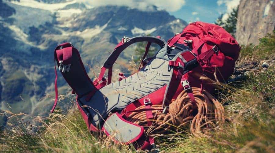 red hiking backpack lying on mountainous hillside intext