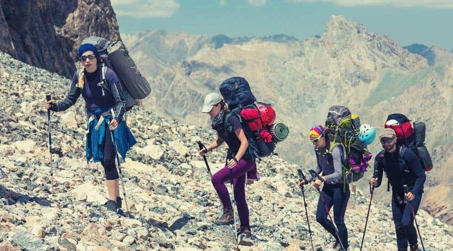 group of hikers with trekking poles walking up mountain scree slopehiking clothing intext
