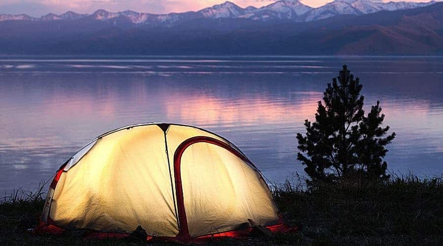 Tent across beautiful sunset on lake - In Text