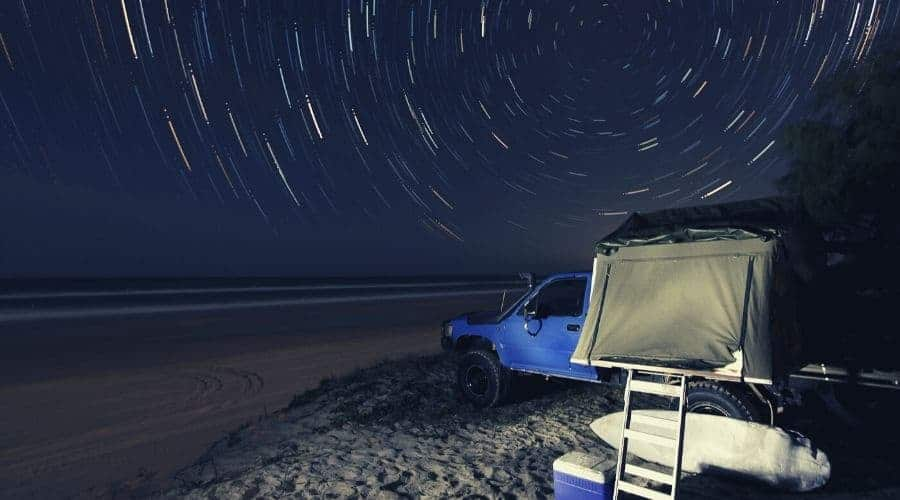 tent on top of suv truck on beach intext