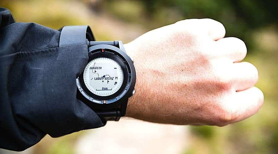 hiker looks at hiking watch altimeter - In Text