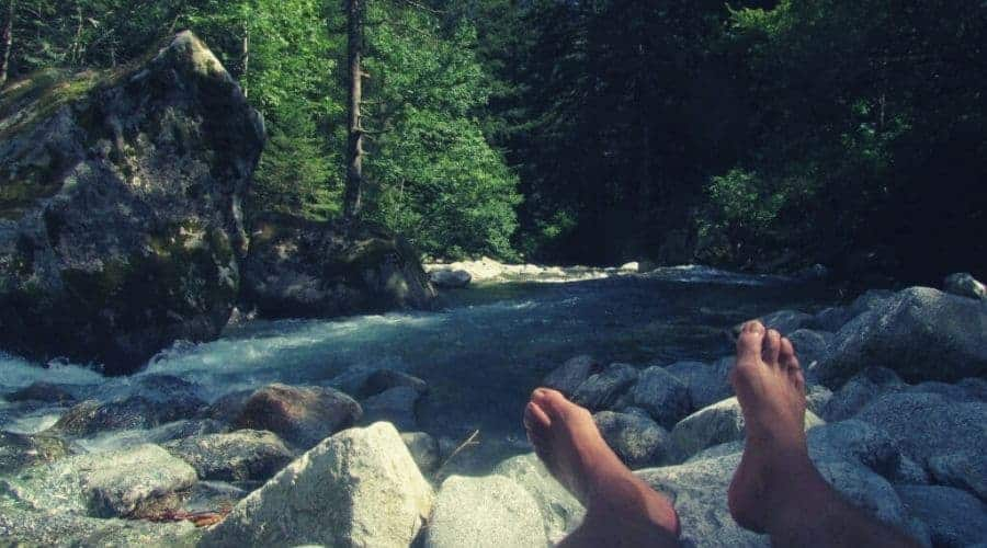 hikers feet enjoy rest by forest river intext