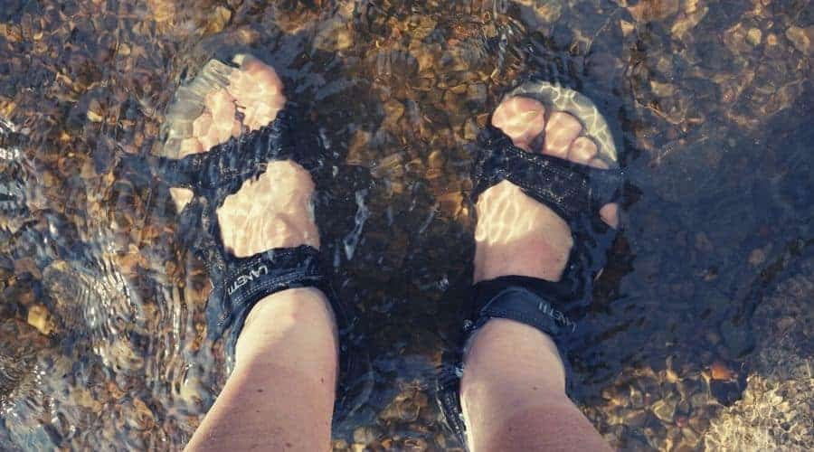 hikers feet sandals in shallow river intext
