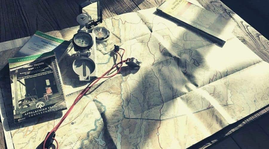 Two compasses and a map sitting on a table intext