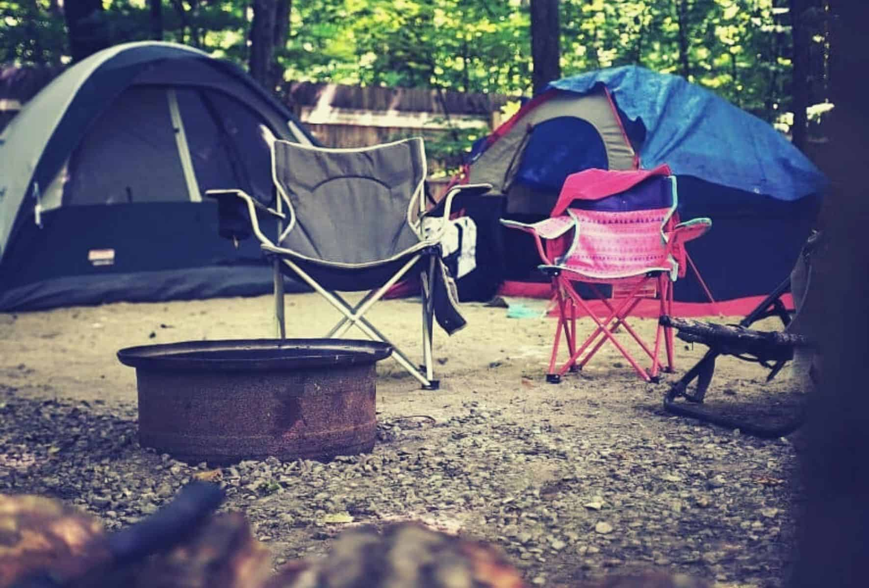 Campsite setup with tents and chairs and fire