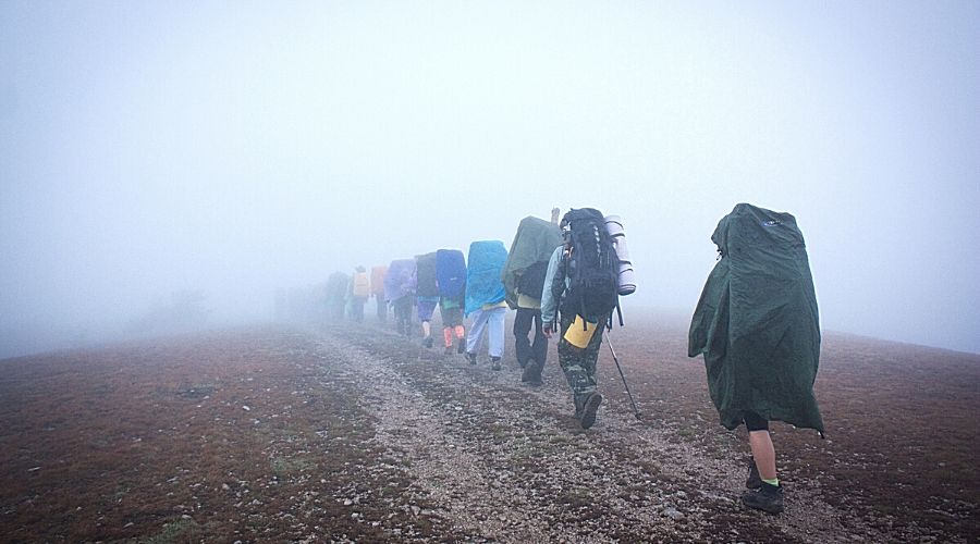 hikers in rain gear walking in mist - In Text
