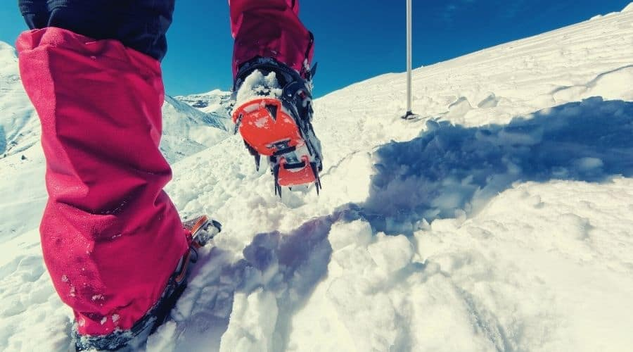 using gaiters and crampons on snowy mountain