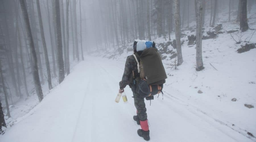 backpacker walk in snowy woods water bottles
