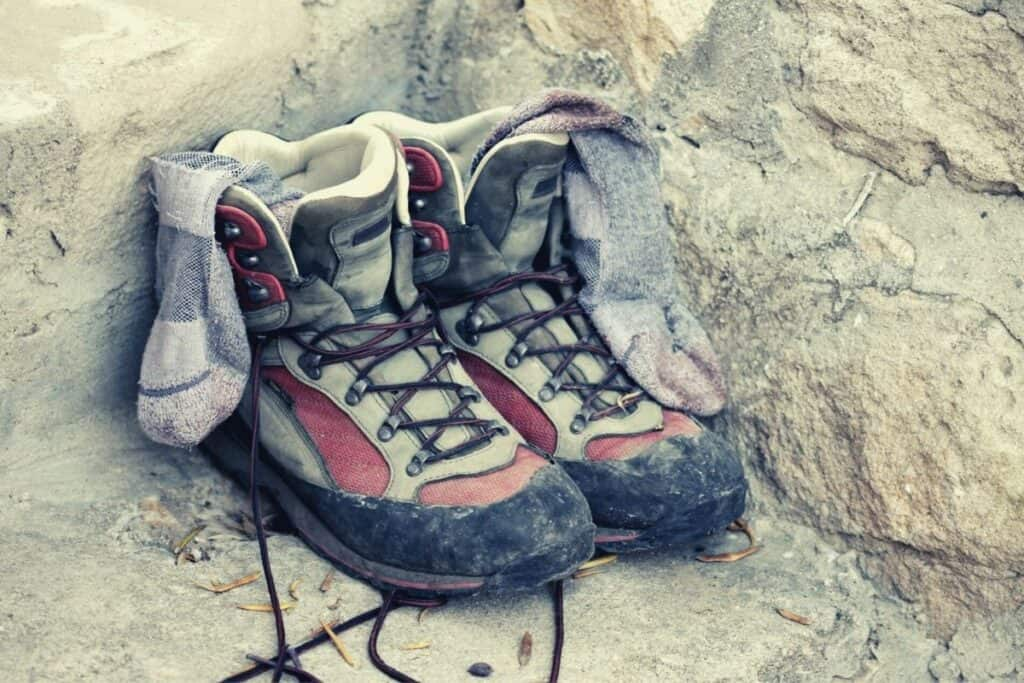 pair of hiking boots and wool socks on rock - benefits of wool socks featimg