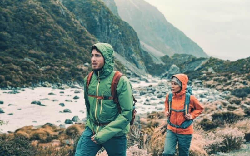 two hikers hiking in rain through valley
