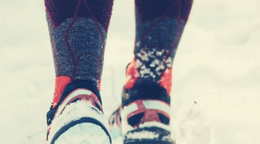 closeup of hiker wearing long socks and boots in snow