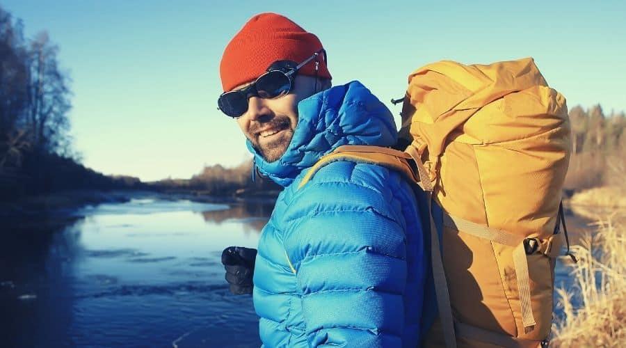 hiker wearing ski goggles down jacket next to lake