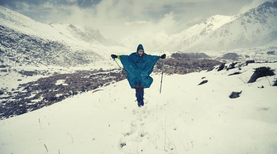 hiker with poles and poncho hiking in deep snow through valley