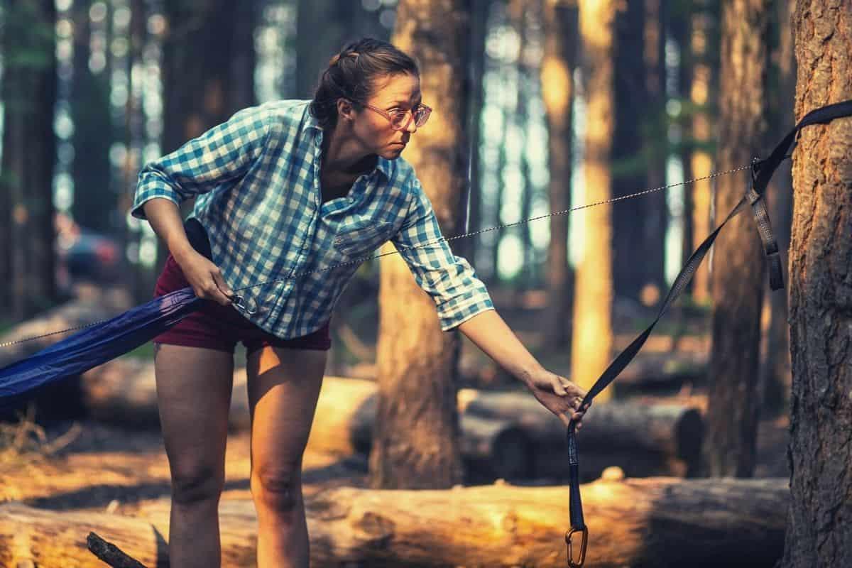 Woman hanging a hammock - how to hang a hammock featimg