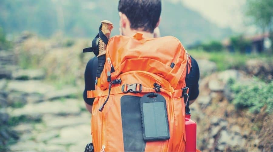 portable solar charger on backpackers backpack