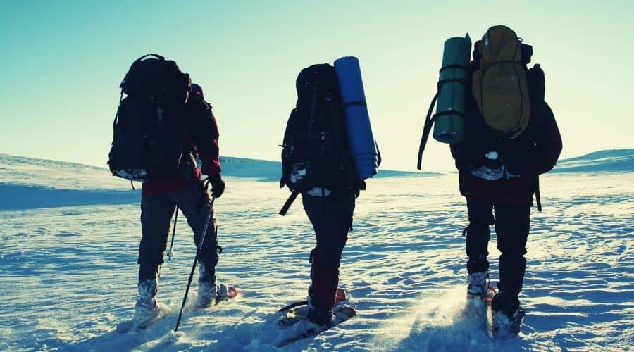 three hikers in snowshoes hiking across snow field