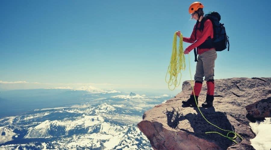 woman preparing rope on mountain ledge