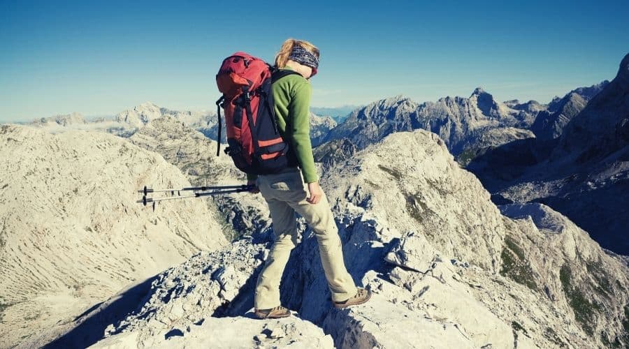 woman walking over rocky outcrop in mountains