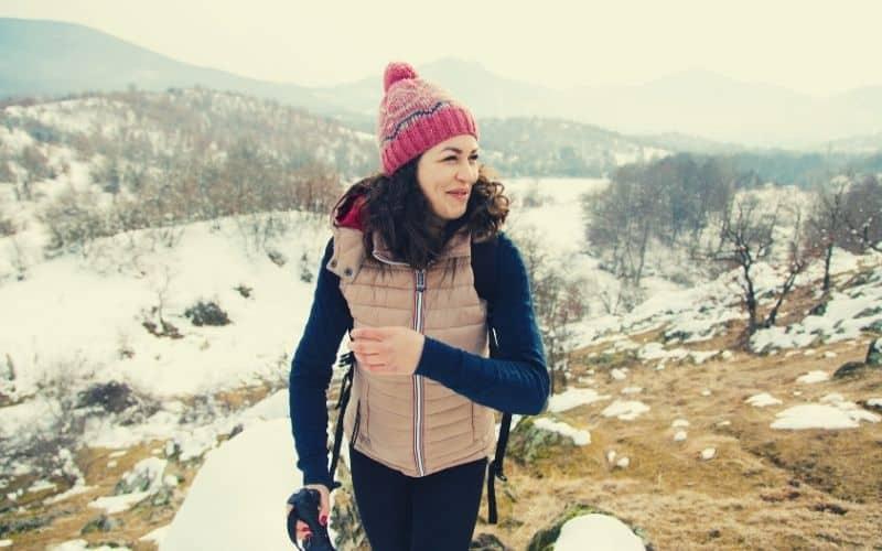 hiker wearing beanie down vest in snowy weather