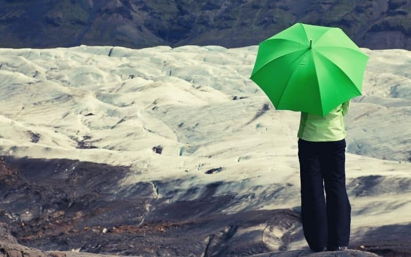woman hiker with umbrella standing in front of glacier