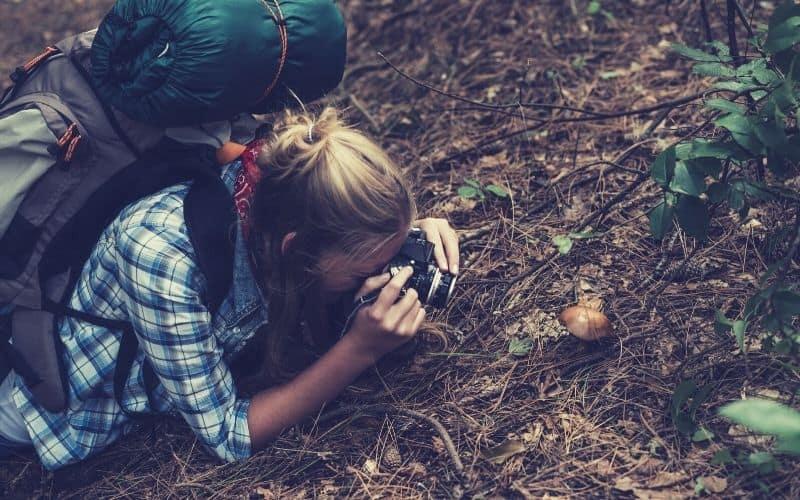 backpacker photographing mushroom