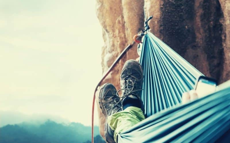 climber hanging in a hammock off a cliff face