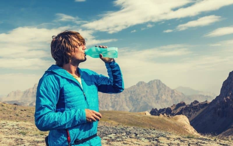 hiker drinking water while wearing lightweight down jacket