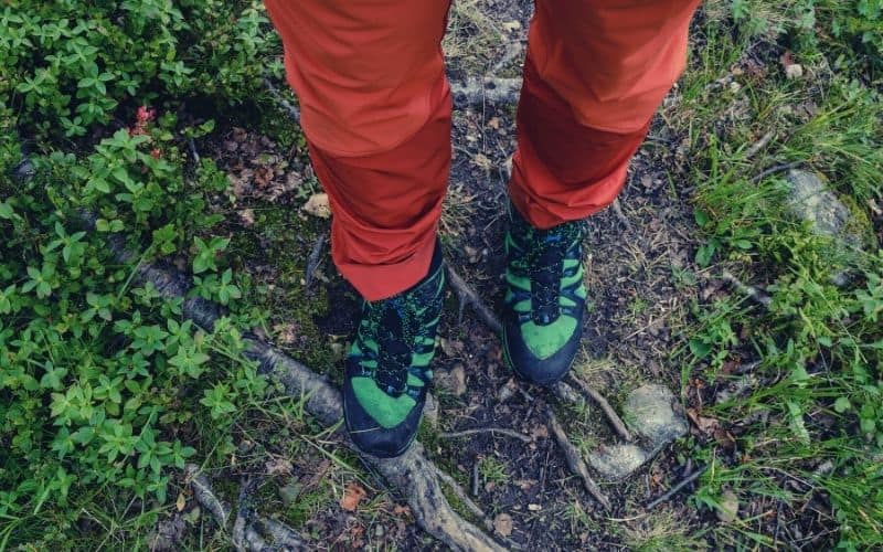 hiking wearing bright red hiking pants and green shoes
