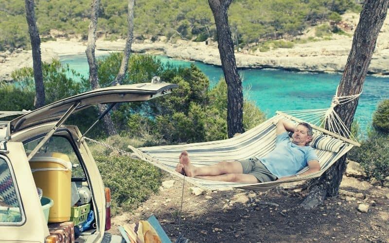 man hanging hammock off car tail gate