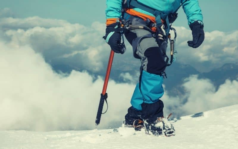 mountaineer with mountaineering pants, gaiters and crampons