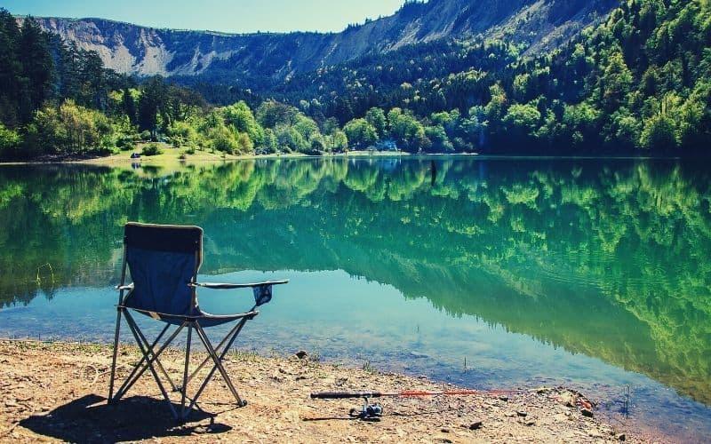 backpacking chair & fishing rod next to beautiful lake