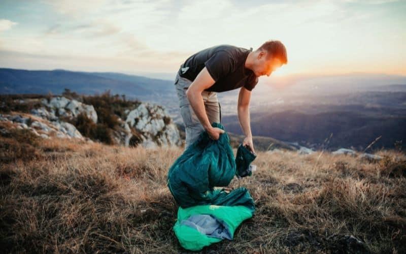 Backpacker packing away sleeping bag