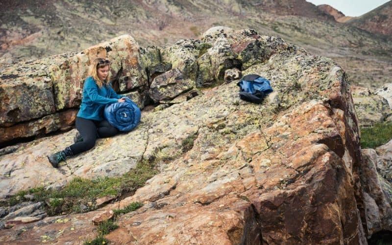 Female Backpacker packing away synthetic sleeping bag