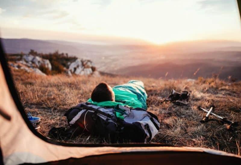 backpacker outside tent in sleeping bag - best sleeping bag feat img
